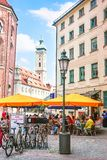 Munich, Germany - May 8, 2013: Bicycles and people at street cafe in the old center of Munich, Germany. Heiliggeistkirche on the. Background royalty free stock photos