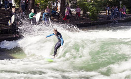 MUNICH, GERMANY - NOVEMBER 1: Surfers train on a man-made wave about 1 metre high in the Eisbach river in English Garden Stock Image