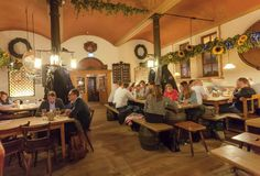 Women and men eating and drinking beer inside traditional restaurant in old Bavarian style stock photography