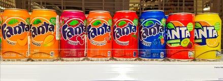 Various bottles, aluminum cans of soft drinks on shelf in supermarket. Stock Photo