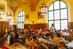 MUNICH, GERMANY - OCTOBER 14, 2017: Interior of main beer restaurant Hofbrauhaus. With tourists and football funs royalty free stock photos