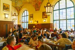 MUNICH, GERMANY - OCTOBER 14, 2017: Interior of main beer restaurant Hofbrauhaus. With tourists and football funs stock photo