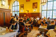 MUNICH, GERMANY - OCTOBER 14, 2017: Interior of main beer restaurant Hofbrauhaus. With tourists and football funs royalty free stock photo