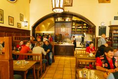 MUNICH, GERMANY - OCTOBER 14, 2017: Interior of main beer restaurant Hofbrauhaus. With tourists and football funs stock photography