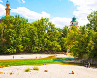 Munich Germany, people relax sun bathing along Isar river in cen Stock Images