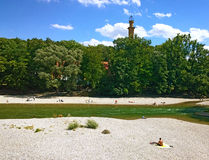 Munich Germany, people sun bathing along Isar river in center ci Stock Photos