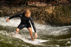 Surfing on the River - Englischer Garten Munich. MUNICH, GERMANY - SEPT 8, 2018: A man surfing in the waves of the Eisbach River in downtown of Munich. It forms royalty free stock photo