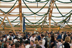 MUNICH, GERMANY - SEPTEMBER 23, 2014: Oktoberfest. Munich: People dressed in traditional costumes sitting in the beer pavilion stock photo