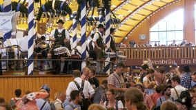 Orchestra band plays inside a large beer tent at the Oktoberfest Festival. Bavaria, Germany. MUNICH, GERMANY, SEPTEMBER 16, 2017: Orchestra band plays inside a stock video footage