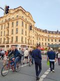 People crossing street on foot and riding bicycles  to and from Royalty Free Stock Photos