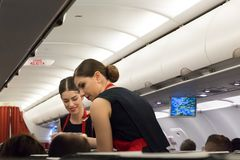 Flight Attendant Serving smiling. Munich, Germany - September 21th, 2017: Two female flight attendants are serving the meal in the economy class of the route Royalty Free Stock Photography