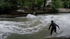 Urban Surfers on a man-made wave on the Eisbach river in the center of Munich. Slow Motion. MUNICH, GERMANY, SEPTEMBER 15, 2017: Urban Surfers on a man-made wave stock video