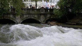 Urban Surfers on a man-made wave on the Eisbach river in the center of Munich. Slow Motion. MUNICH, GERMANY, SEPTEMBER 15, 2017: Urban Surfers on a man-made wave stock video footage