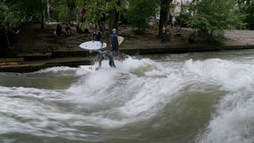 Urban surfers ride the standing wave on the Eisbach River, Munich, Germany. MUNICH, GERMANY, SEPTEMBER 15, 2017: Urban surfers ride the standing wave on the stock video footage
