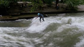 Urban surfers ride the standing wave on the Eisbach River, Munich, Germany. MUNICH, GERMANY, SEPTEMBER 15, 2017: Urban surfers ride the standing wave on the stock video
