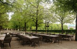 Munich green park in city center with the beer garden. Munich - Hofgarten green park in city center early in the morning, with the beer garden tables ready for stock images