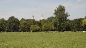 Munich horisont från Englischer Garten, Tyskland Lokaler och turister tycker om en varm sommardag i parkera lager videofilmer