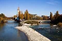 Munich, Isar river and Deutsches Museum. Beautiful autumnal view of the blue waters of Isar river in Munich, with the tower of the Deutsches Museum and the Royalty Free Stock Photo