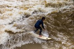 MUNICH-JUNE 14. Surfer man on the Eisbach in the English Garden in Munich on June 14, 2018 in Munich, Germany. Stock Photo