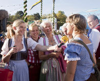 Munich, Oktoberfest, TV speaker interviews a girl. Munich, Oktoberfest. TV speaker interviews a girl with other women smiling around, all wearing the traditional royalty free stock image