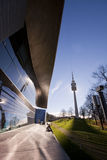 Munich, Olympia Park: BMW world and Olympia tower. On a sunny day of November people enjoy the sun at Munich Olympia Park sitting in front of BMW world with the Royalty Free Stock Photos