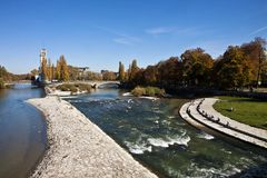 Munich, panoramic view of Isar river and Deutsches Museum. Beautiful panoramic autumnal view of the blue waters of Isar river in Munich, with the tower of the Stock Photography