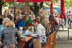 Munich, people seat at beer garden in Viktualienmarkt. Munich, Germany - people have leisure time, Bavarian food and beer at open air beer garden in stock photo