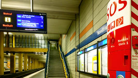 Munich subway station with SOS spot and train departures informa. MUNICH, GERMANY - AUGUST 8, 2015 - Interior of subway station in Munich with SOS emergency spot Stock Image