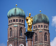 Munich, Germany. The main symbols of Munich, Germany: the golden statue of Saint Mary on its column in the Marienplatz and the two onion shaped towers of the stock photos