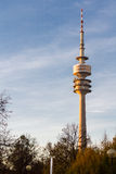 Munich TV Transmission Tower in Warm Sunlight. Architectural View of Television Transmission Tower Standing Tall Above Bare Tree Tops at Sunrise or Sunset with Stock Images