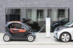 Munich Tyskland Juni 25, 2016: Två elbilar, Renault och BMW, laddas upp på inkopplingsstationen framme av modern byggnad Arkivfoton