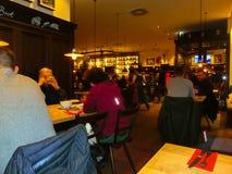 Munich Tyskland - Maj 01, 2017: Folket som vilar på traditionella bayerska Tracht i restaurangen eller baren Stubn med ölkrus Royaltyfri Foto