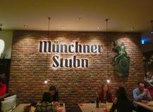 Munich Tyskland - Maj 01, 2017: Folket som vilar på traditionella bayerska Tracht i restaurangen eller baren Stubn med ölkrus Royaltyfria Foton