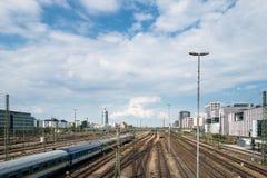 MUNICH Tyskland - Maj 10, 2018: Järnvägsstationsikt med drevet och molnig himmel Lopp och trans arkivfoton