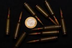 Munición del rifle alrededor de una moneda euro en fondo negro Simboliza la guerra para el dinero y uno de los problemas del ` s  fotografía de archivo