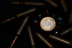 Munición del rifle con muchas piedras preciosas alrededor de una moneda euro en fondo negro Simboliza la guerra para el dinero y  imagenes de archivo