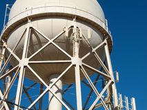 Municipal Water Tower. A municipal water tank showing the steel beam construction of its support tower shot against a clear blue sky Royalty Free Stock Photos