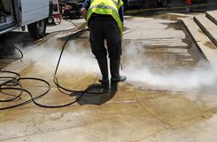 Cleaning the pavement of the street with pressurized water. Municipal worker cleaning street sidewalks with hot pressurized water Royalty Free Stock Image