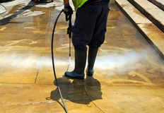 Cleaning the pavement of the street with pressurized water. Municipal worker cleaning street sidewalks with hot pressurized water Stock Photography
