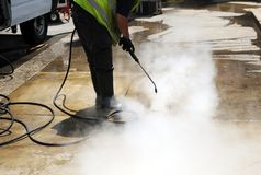Municipal worker cleaning street sidewalks with hot pressurized water. Cleaning the pavement of the street with pressurized water Stock Photo