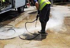 Municipal worker cleaning street sidewalks with pressurized water. Clean the pavement of the street with  hot pressurized water Royalty Free Stock Photo