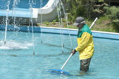 Municipal worker, Istanbul. Istanbul, Turkey - Municipal worker cleaning the decorative pool and fountains inside the public Macka Park in Istanbul Royalty Free Stock Photo