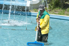 Municipal worker, Istanbul. Istanbul, Turkey - Municipal worker cleaning the decorative pool and fountains inside the public Macka Park in Istanbul Royalty Free Stock Image