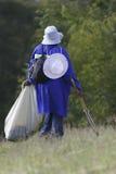 Municipal worker picking up litter. Municipal employee wearing a blue overall picking up litter outdoors Stock Photography