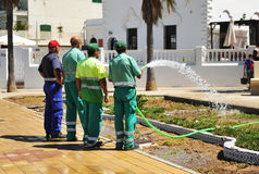 Municipal workers watering a garden city Royalty Free Stock Photography