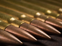 Munition closeup. Bullets in a row on the wooden surface, closeup shot,shallow DOF with focus on the second bullet, useful for themes such as war,terrorism,crime Royalty Free Stock Images