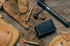 Munizioni, vecchio guanto tattico, ginocchiere e detailes della carabina su Th Immagini Stock