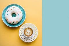 Munk bredvid en kopp av doftande kaffe eller cappuccino på en gul bakgrund Närliggande ställe för text Arkivbilder