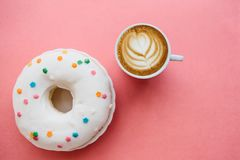 Munk bredvid en kopp av doftande kaffe eller cappuccino på en röd bakgrund Arkivfoto