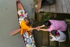 Munk Collecting Alms på den Amphawa floden arkivbild
